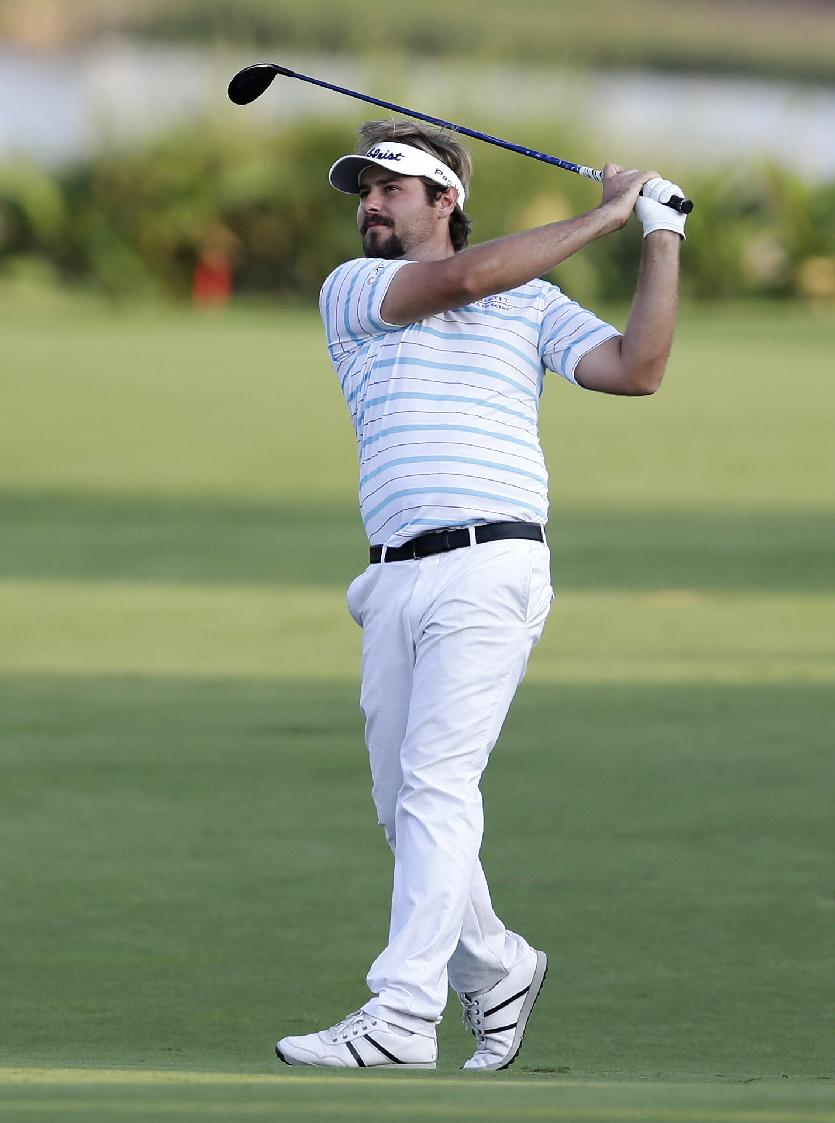 Victor Dubuisson of France follows his ball during the 3rd round of the World Tour Golf Championship in Dubai, United Arab Emirates, Saturday, Nov. 16, 2013
