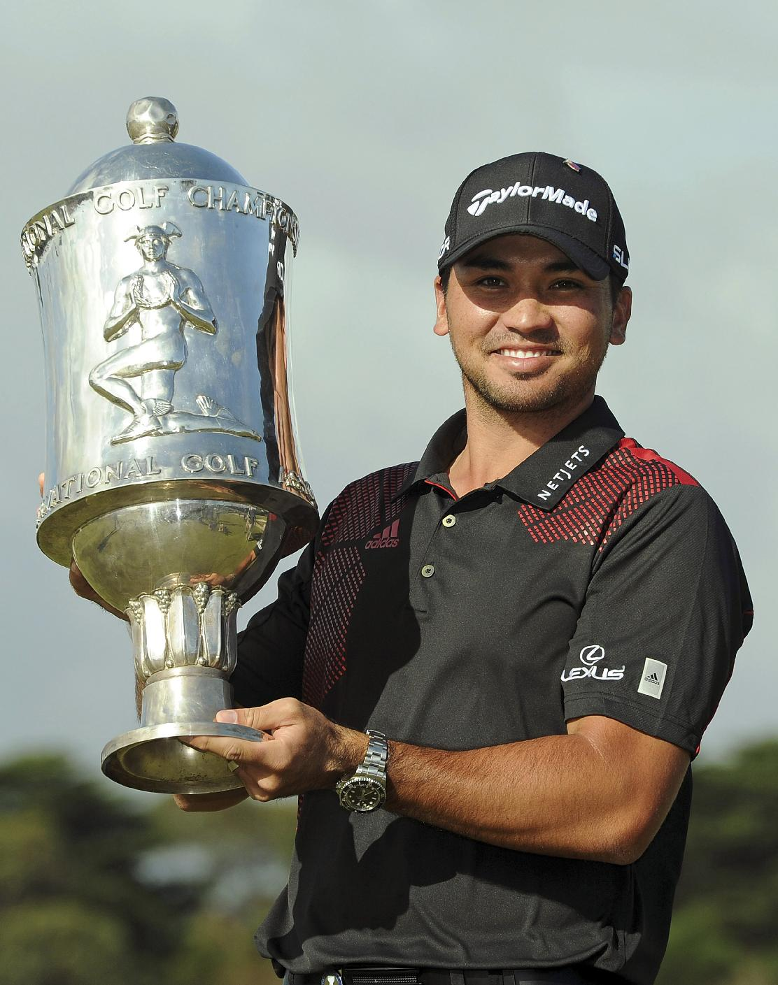 Jason Day of Australia poses with the trophy for photographers after winning the individual event at the World Cup of Golf at Royal Melbourne Golf Course in Australia, Sunday, Nov. 24, 2013