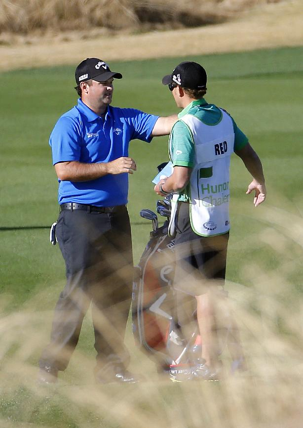 Patrick Reed, left, stretches with his caddie on the 12th fairway during the third round of the Humana Challenge PGA golf tournament on the Nicklaus Private course at PGA West, Saturday, Jan. 18, 2014, in La Quinta, Calif