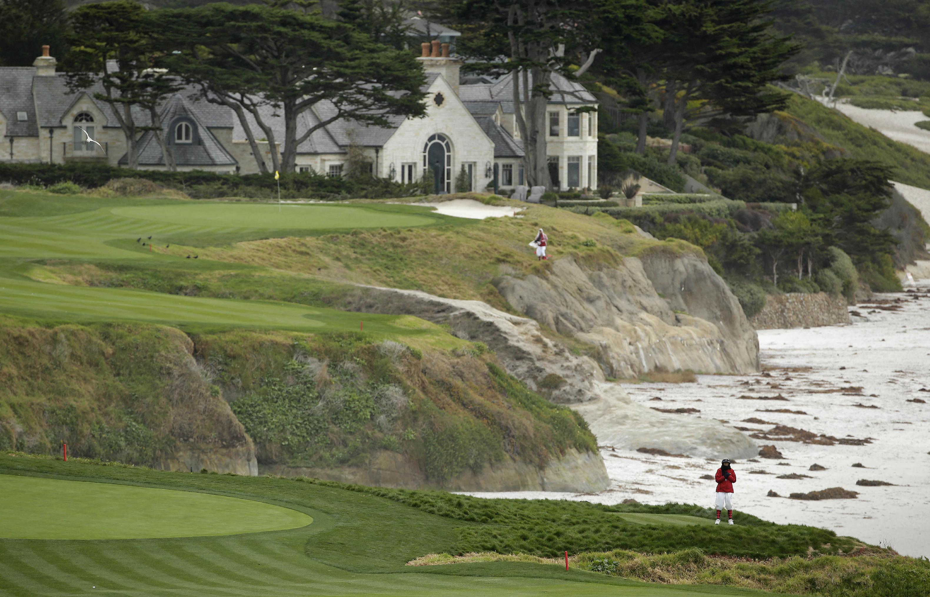 In this photo taken Friday, Feb. 7, 2014, a marshal at lower right stands on an optional 10th tee of the Pebble Beach Golf Links with the 10th green in the background during the second round of the AT&T Pebble Beach Pro-Am golf tournament in Pebble Beach, Calif. The optional 10th tee is to the right of the ninth green. Officials discovered it in old photos and restored it after they rebuilt the ninth green. Pebble Beach wants the USGA to look at it as a possible forward tee in the 2019 U.S. Open