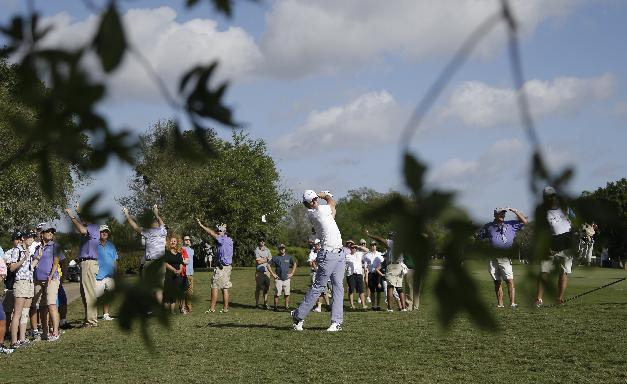 Rory McIlroy of Northern Ireland hits from the eighth fairway during the first round of the Cadillac Championship golf tournament Friday, March 7, 2014, in Doral, Fla.  A severe thunderstorm delayed play on Thursday