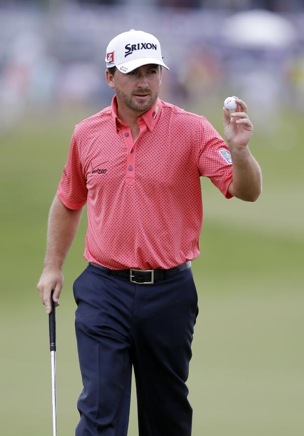 Graeme McDowell, of Northern Ireland, shows his ball after making birdie in the second hole during the final round of the Cadillac Championship golf tournament on Sunday, March 9, 2014, in Doral, Fla