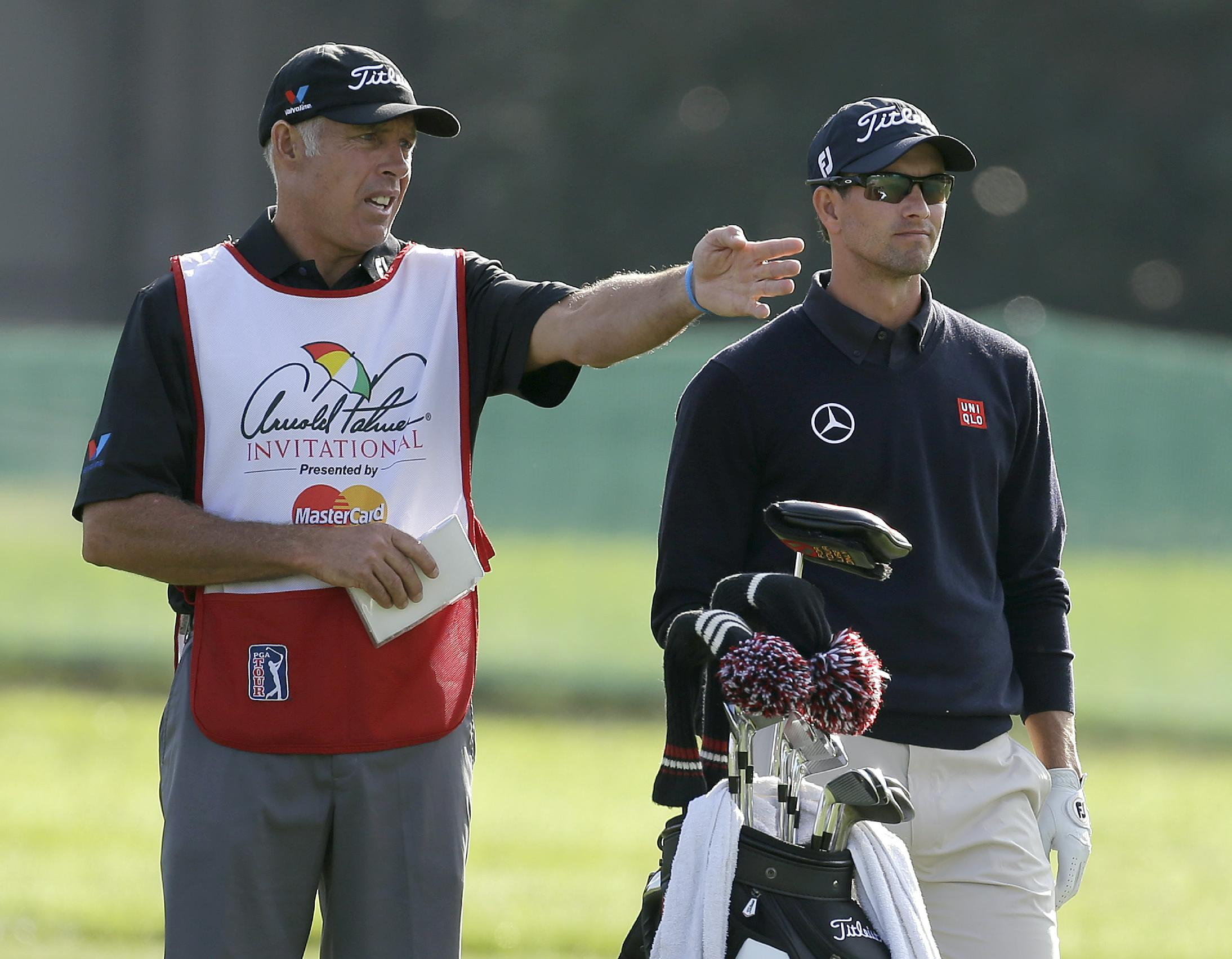 Caddie Steve Williams, left, gestures as he talks to Adam Scott, of Australia, on the 16th fairway during the first round of the Arnold Palmer Invitational golf tournament at Bay Hill Thursday, March 20, 2014, in Orlando, Fla