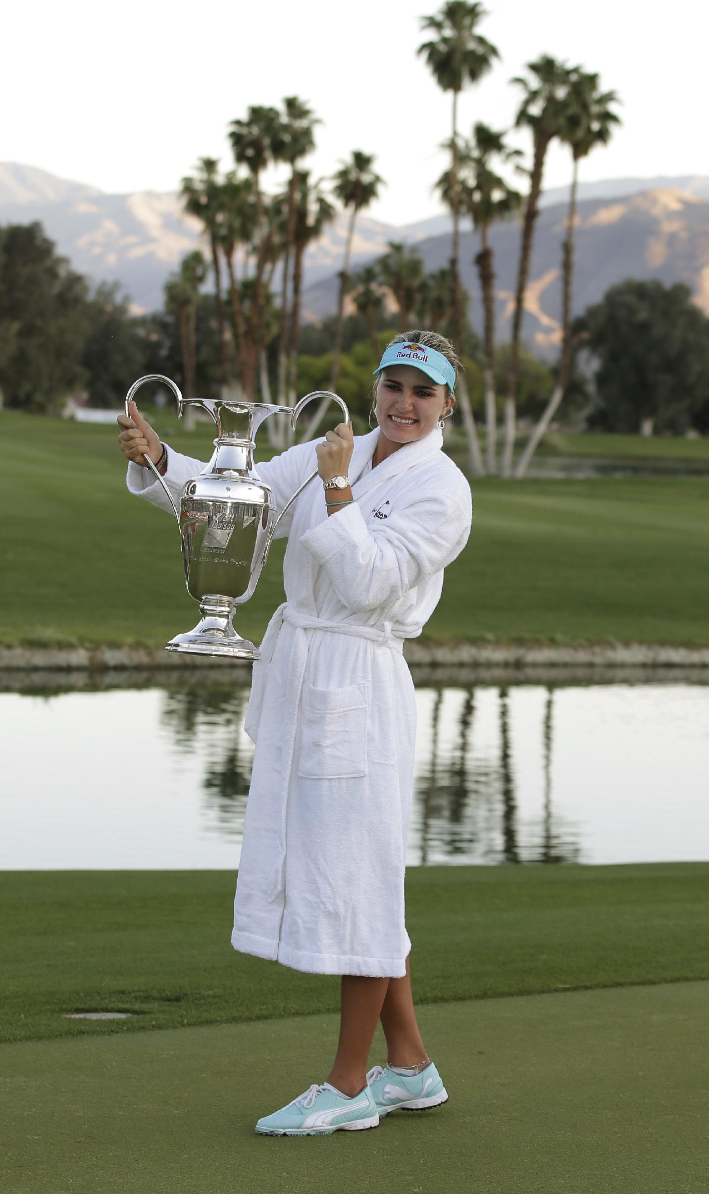 Lexi Thompson holds up the trophy after winning the Kraft Nabisco Championship golf tournament Sunday, April 6, 2014, in Rancho Mirage, Calif. Thompson defeated Michelle Wie by three strokes