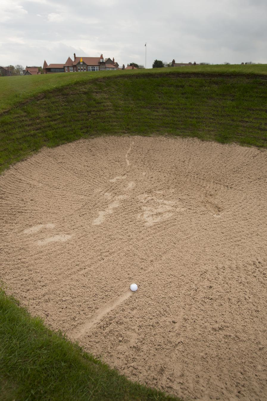 The clubhouse at Royal Liverpool Golf Club stands in the background as a ball lies in the bunker on the 18th hole before the British Open golf championships, Hoylake, England, Wednesday, April 23, 2014. The 2014 Open Championship which will be played at Royal Liverpool from July 17-20, 2014