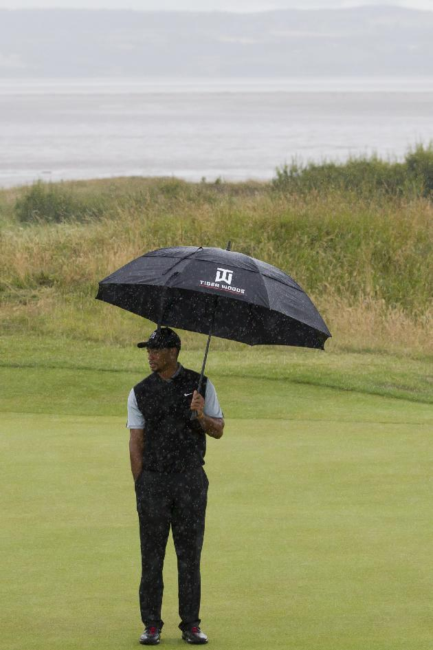 Tiger Woods of the US stands in the rain on the 14th green during a practice round at Royal Liverpool Golf Club prior to the start of the British Open Golf Championship, in Hoylake, England, Saturday, July 12, 2014. The 2014 Open Championship starts on Thursday, July 17