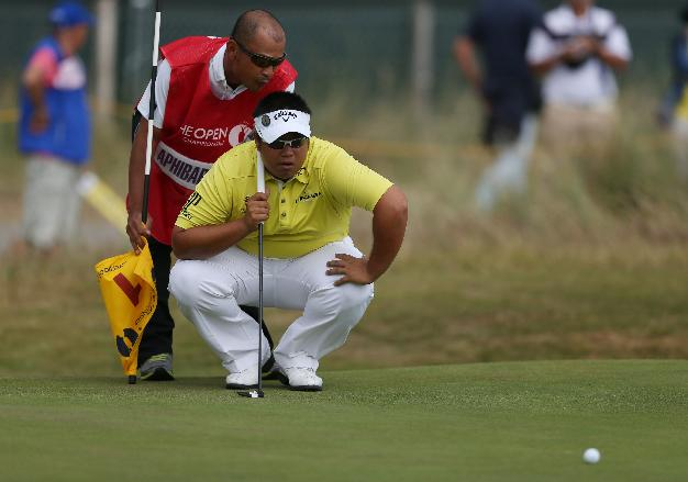 Kiradech Aphibarnrat of Thailand and his caddie line up a putt on the 1st green during the second day of the British Open Golf championship at the Royal Liverpool golf club, Hoylake, England, Friday July 18, 2014