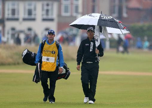 Byeong Hun An of Korea walks along the 3rd fairway with his caddie Dean Smith as rain falls during the third day of the British Open Golf championship at the Royal Liverpool golf club, Hoylake, England, Saturday July 19, 2014