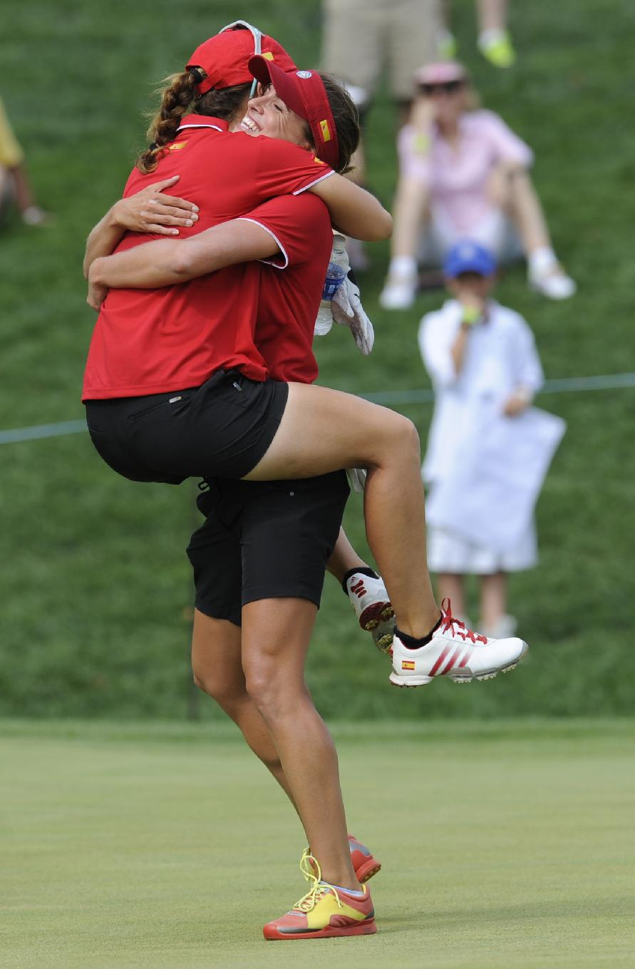 Belen Mozo lifts Beatriz Recari, both of Spain, after making a birdie on the 16th hole to give Spain the win during the final round of the International Crown golf tournament on Sunday, July 27, 2014, in Owings Mills, Md
