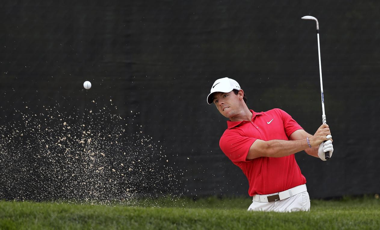 Rory McIlroy, of Northern Ireland, hits from a bunker on the 13th hole during the first round of play at The Barclays golf tournament Thursday, Aug. 21, 2014, in Paramus, N.J