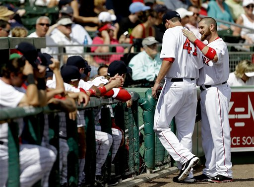 John Lackey, left, receives a pat on the back from teammate Jonny Gomes as he heads to the dugout after pitching the first inning of an exhibition spring training baseball game against the Tampa Bay Rays, Saturday, Feb. 23, 2013, Fort Myers, Fla. (AP Photo/David Goldman)