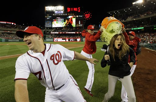Washington Nationals starting pitcher Jordan Zimmermann (27) dodges the Gatorade, but MASN's sideline reporter Julie Alexandria, wasn't so lucky as relief pitchers Drew Storen, second from left,  and Ryan Mattheus pour the Gatorade, after a baseball game against the Cincinnati Reds at Nationals Park Friday, April 26, 2013, in Washington. Zimmermann threw a one hit complete game shutout and the Nationals won 1-0.