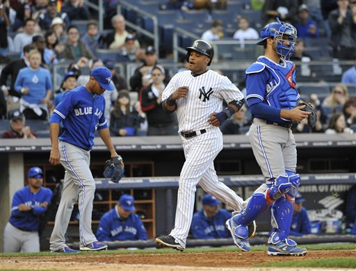 New York Yankees' Robinson Cano  scores past Toronto Blue Jays relief pitcher Esmil Rogers, left, and  catcher J.P. Arencibia off a single by  Vernon Wells in the seventh inning of a baseball game at Yankee Stadium on Saturday, April 27, 2013 in New York.