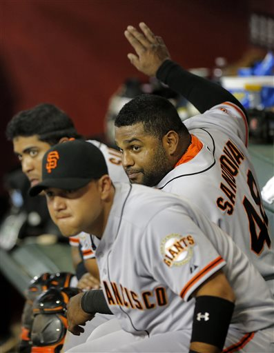 San Francisco Giants players, from left, Hector Sanchez, Pablo Sandoval and Guillermo Quiroz watch the Arizona Diamondbacks hit during the fifth inning of a baseball game, Tuesday, April 30, 2013, in Phoenix. 