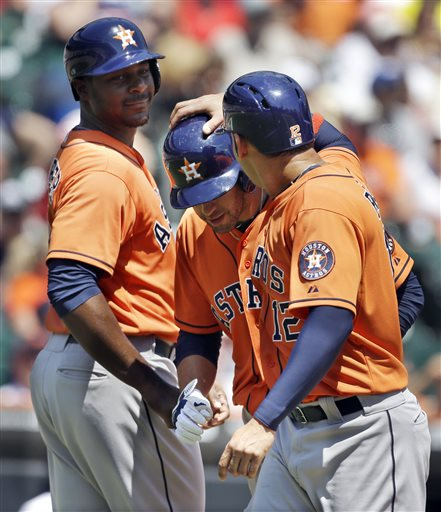 Houston Astros' J.D. Martinez, center, is congratulated by Carlos Pena, right, and Chris Carter after hitting a three-run home run off Detroit Tigers pitcher Max Scherzer during the fourth inning of a baseball game in Detroit, Wednesday, May 15, 2013