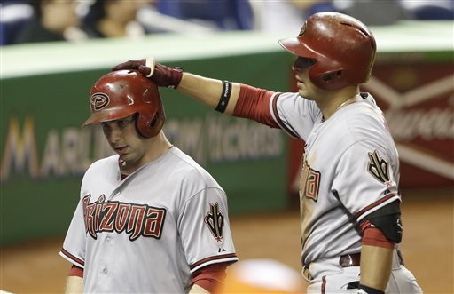 Arizona Diamondbacks' Paul Goldschmidt, left, is congratulated by teammate Martin Prado, right, after scoring on a single by Cody Ross in the ninth inning during a baseball game against the Miami Marlins in Miami, Friday, May 17, 2013. The Diamondbacks defeated the Marlins 9-2