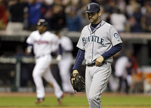 Seattle Mariners relief pitcher Lucas Luetge, foreground, walks off the field after giving up a game-winning, three-run home run to Cleveland Indians' Jason Kipnis in the 10th inning of a baseball game on Friday, May 17, 2013, in Cleveland. Kipnis' home run gave the Indians a 6-3 win