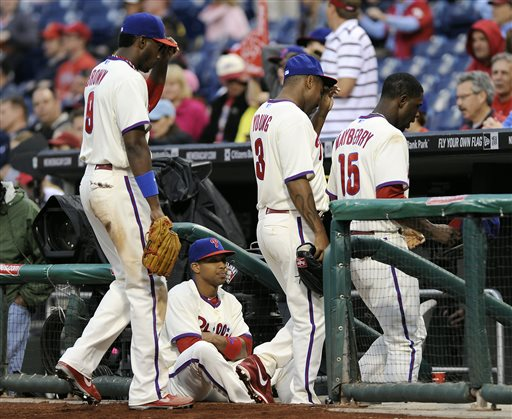Philadelphia Phillies' Ben Revere, center, sits in stairwell of the dugout as Domonic Brown (9), Delmon Young (3) and John Mayberry (15) walk off the field in the ninth inning of a baseball game on Saturday, May 18, 2013, in Philadelphia. The Reds won 10-0