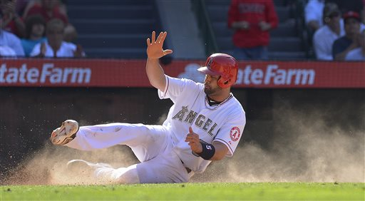 Los Angeles Angels' Albert Pujols (5) scores on a sacrifice fly ball by Alberto Callaspo against the Chicago White Sox during the eighth inning of a baseball game, Saturday, May 18, 2013, in Anaheim, Calif. The Angels won 12-9