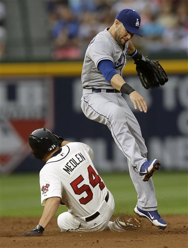Los Angeles Dodgers second baseman Skip Schumaker, right, avoids Atlanta Braves' Kris Medlen (54) while turning a double play on a Andrelton Simmons ground ball in the third inning of a baseball game on Saturday, May 18, 2013, in Atlanta