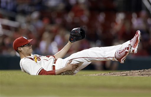 St. Louis Cardinals relief pitcher Joe Kelly falls after Milwaukee Brewers' Ryan Braun hit a single during the 10th inning of a baseball game Saturday, May 18, 2013, in St. Louis