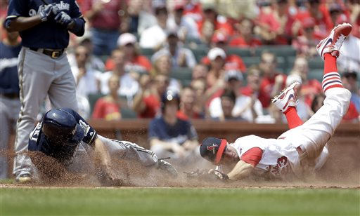 St. Louis Cardinals third baseman David Freese, right, tags Milwaukee Brewers' Norichika Aoki out at home after Aoki was caught stealing home during the first inning of the MLB National League baseball game Sunday, May 19, 2013, in St. Louis