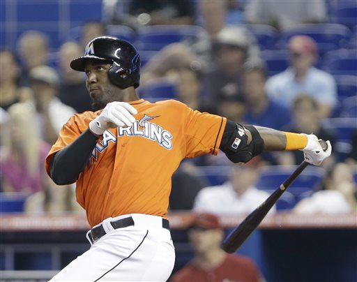 Miami Marlins' Marcell Ozuna watches his ball as he hits a double, scoring Adeiny Hechavarria and Derek Dietrich, during the  sixth inning of a baseball game against the Arizona Diamondbacks, Sunday, May 19, 2013, in Miami