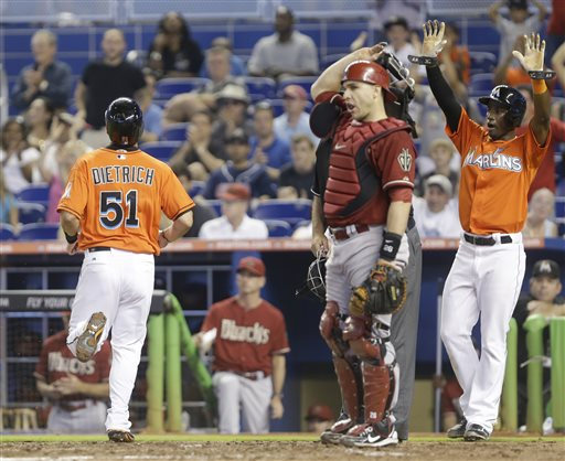 Miami Marlins' Adeiny Hechavarria, right, gestures to Marcell Ozuna (not shown) to hold up on second base as Derek Dietrich (51) crosses home plate and Arizona Diamondbacks catcher Miguel Montero looks on during the sixth inning of a baseball game on Sunday, May 19, 2013, in Miami. Ozuna scored Hechavarria and Dietrich on a double and the Marlins went on to defeat the Diamondbacks 2-1