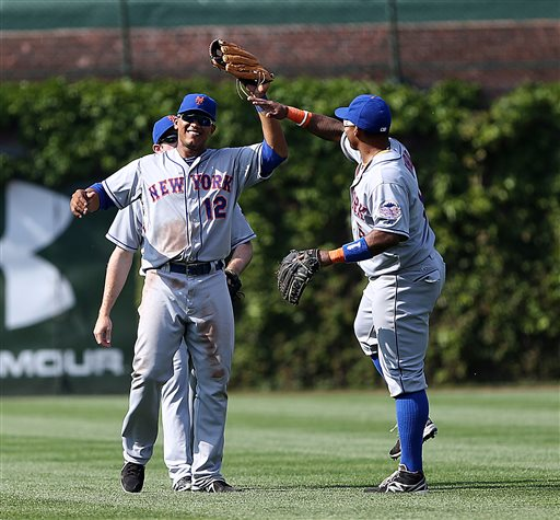 New York Mets outfielders Juan Lagares(12) Marlon Byrd and Mike Baxter celebrate as the Mets beat the  Chicago Cubs 4-3 in the MLB National League baseball game in Chicago on Sunday, May 19, 2013