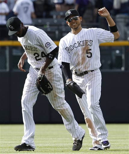 Colorado Rockies left fielder Carlos Gonzalez, right, celebrates with center fielder Dexter Fowler after their 5-0 victory over the San Francisco Giants in a baseball game in Denver, Sunday, May 19, 2013