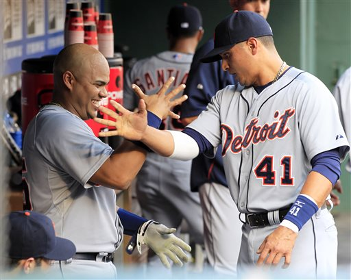 Detroit Tigers catcher Brayan Pena, left, and teammate Victor Martinez, right,  trade hand gestures in the dugout before the start of a baseball game against the Texas Rangers Sunday, May 19, 2013, in Arlington