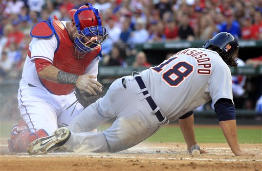 Texas Rangers catcher Geovany Soto, left, checks to see that he still has the ball, after tagging out Detroit Tigers shortstop Matt Tuiasosopo, right, at home plate during the second inning of a baseball game Sunday, May 19, 2013, in Arlington
