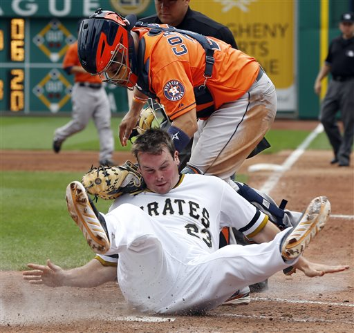 Pittsburgh Pirates' Travis Snider, bottom, rolls into Houston Astros catcher Carlos Corporan after being tagged out trying to score from second on a single by Gaby Sanchez in the sixth inning of a baseball game on Sunday, May 19, 2013, in Pittsburgh