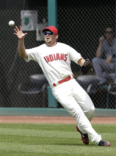 Cleveland Indians' Ryan Raburn bare hands the ball hit by Seattle Mariners' Brendan Ryan in the seventh inning of a baseball game, Monday, May 20, 2013, in Cleveland. Ryan was safe at first base