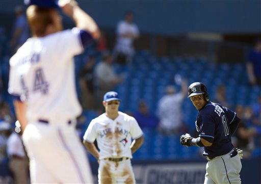 Tampa Bay Rays' Yunel Escobar, right, rounds the bases after hitting a two-run home run off Toronto Blue Jays Casey Janssen, left, during the ninth inning of a baseball game in Toronto on Monday May 20, 2013
