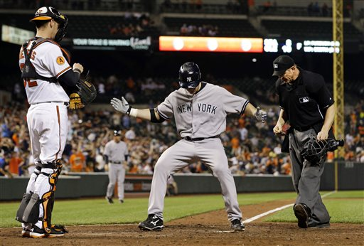 New York Yankees designated hitter Travis Hafner, center, crosses home plate after hitting a solo home run in the ninth inning of a baseball game against the Baltimore Orioles in Baltimore, Monday, May 20, 2013. New York won 6-4 in 10 innings