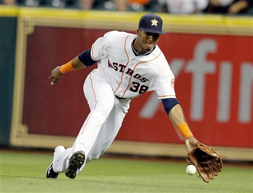 Houston Astros right fielder Jimmy Paredes comes up short on a shallow fly ball from Kansas City Royals right fielder Jeff Francoeur  in the eighth inning of a baseball game, Monday, May 20, 2013, in Houston