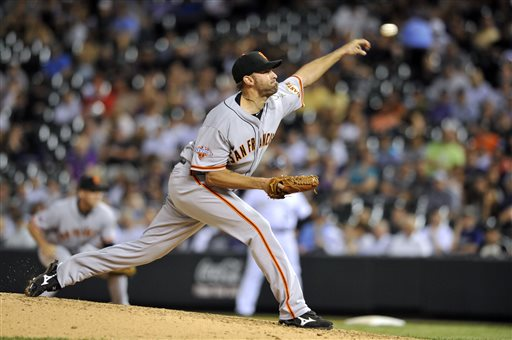 In this photo taken May 16, 2013, San Francisco Giants relief pitcher Jeremy Affeldt throws against the Colorado Rockies during the seventh inning of a baseball game in Denver. Affeldt arrived in San Francisco five years ago determined to get rid of his negative feelings toward the gay population. The Giants pitcher reveals these former thoughts in his recently released book,