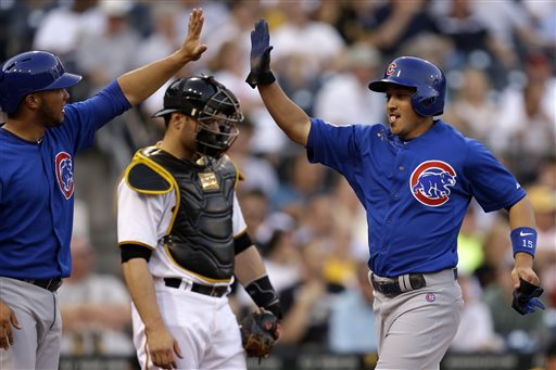 Pittsburgh Pirates catcher Russell Martin, center, waits as Chicago Cubs'  Darwin Barney, right, is greeted by teammate Welington Castillo, left, after both scored on a double by Cubs starting pitcher Matt Garza during the second inning of a baseball in Pittsburgh Tuesday, May 21, 2013