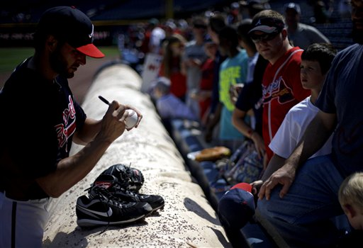 Atlanta Braves pitcher Brandon Beachy, left, signs autographs for fans before the start of a baseball game against the Minnesota Twins, Wednesday, May 22, 2013, in Atlanta