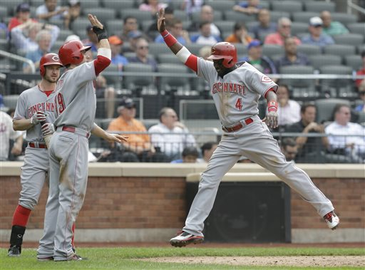 Cincinnati Reds' Jack Hannahan, left, looks on as Brandon Phillips, right, celebrates with Joey Votto after they scored on a single by Todd Frazier during the ninth inning of a baseball game against the New York Mets at Citi Field Wednesday, May 22, 2013, in New York. The Reds won 7-4