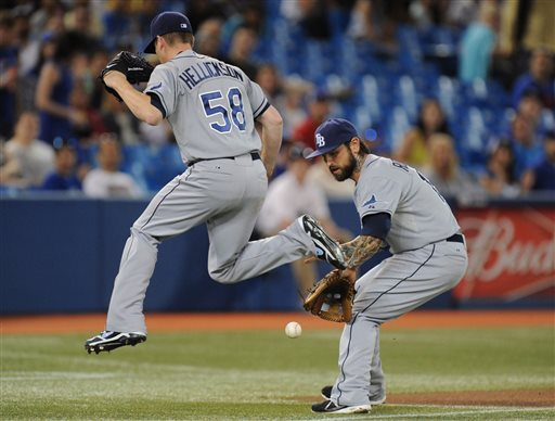 Tampa Bay Rays pitcher Jeremy Hellickson jumps out of the way as Rays third baseman Ryan Roberts fields a ground ball against the Toronto Blue Jays during the first inning of a baseball game in Toronto, Wednesday, May 22, 2013