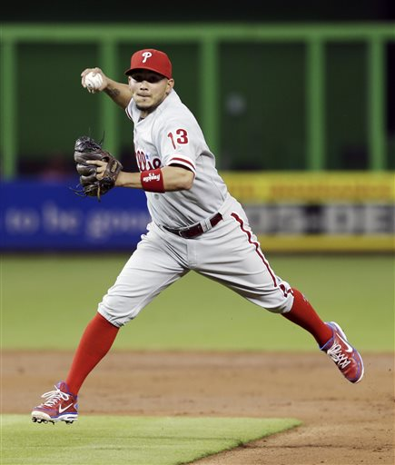 Philadelphia Phillies second baseman Freddy Galvis (13) prepares to throw out Miami Marlins' Derek Dietrich at first base in the first inning of a baseball game in Miami, Wednesday, May 22, 2013
