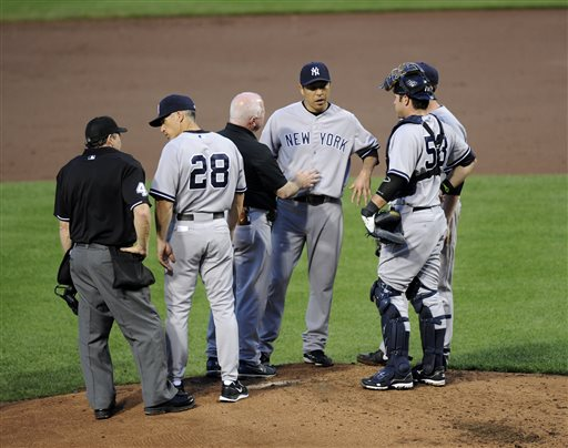 New York Yankees starting pitcher Hiroki Kuroda, second from right, of Japan, is tended to by a trainer as New York Yankees catcher Austin Romine, right, and manager Joe Girardi (28) watch during the second inning of a baseball game, Wednesday, May 22, 2013, in Baltimore