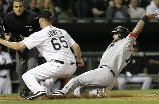 Boston Red Sox's Mike Napoli, right, scores after a passed ball as Chicago White Sox relief pitcher Nate Jones (65) waits for the ball during the eighth inning of a baseball game in Chicago, Wednesday, May 22, 2013
