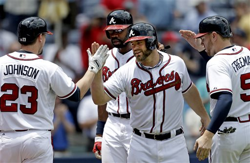In this photo taken Wednesday, May 22, 2013, Atlanta Braves' Evan Gattis, second from right, is greeted by teammates from left, Chris Johnson, Jason Heyward, and Freddie Freeman after hitting a grand slam in the fourth inning of a baseball game against the Minnesota Twins in Atlanta.  It's hard not to get caught up in this modern-day tale, a guy who quit baseball for nearly four years, yet found his way back. Gattis made the Braves as a non-roster player, and has become a downright sensation as a 26-year-old rookie