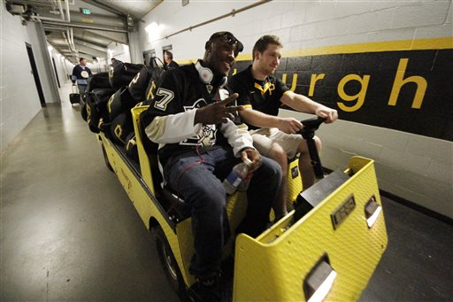 Pittsburgh Pirates' Starling Marte, left, hitches a ride to the team bus for the trip to Milwaukee wearing a Pittsburgh Penguins hockey sweater after a 4-2 win over the Chicago Cubs in a baseball game in Pittsburgh Thursday, May 23, 2013. The entire Pirates team wore Penguins jerseys for their trip in support of the Pittsburgh Penguins in the NHL hockey Stanley Cup playoffs
