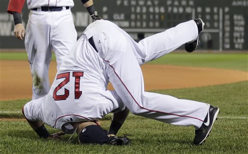 Boston Red Sox first baseman Mike Napoli (12) lands on his head while missing the catch on a foul by Cleveland Indians' Yan Gomes in the seventh inning of a baseball game at Fenway Park in Boston, Thursday, May 23, 2013