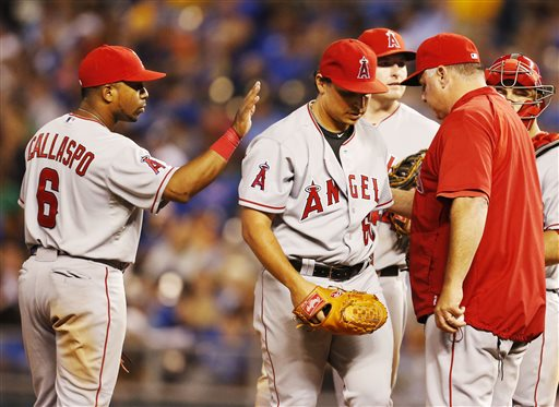 Los Angeles Angels third baseman Alberto Callaspo (6) congratulates starting pitcher Jason Vargas (60) as manager Mike Scioscia, right, takes Vargas out during the eighth inning of a baseball game against the Kansas City Royals at Kauffman Stadium in Kansas City, Mo., Friday, May 24, 2013. The Angels defeated the Royals 5-2