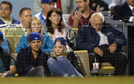 Actor Taylor Lautner, left, and Sara Hicks, center, watch the Los Angeles Dodgers play the St. Louis Cardinals during a baseball game as former Dodgers manager Tommy Lasorda, right, appears to sleep, Friday, May 24, 2013, in Los Angeles